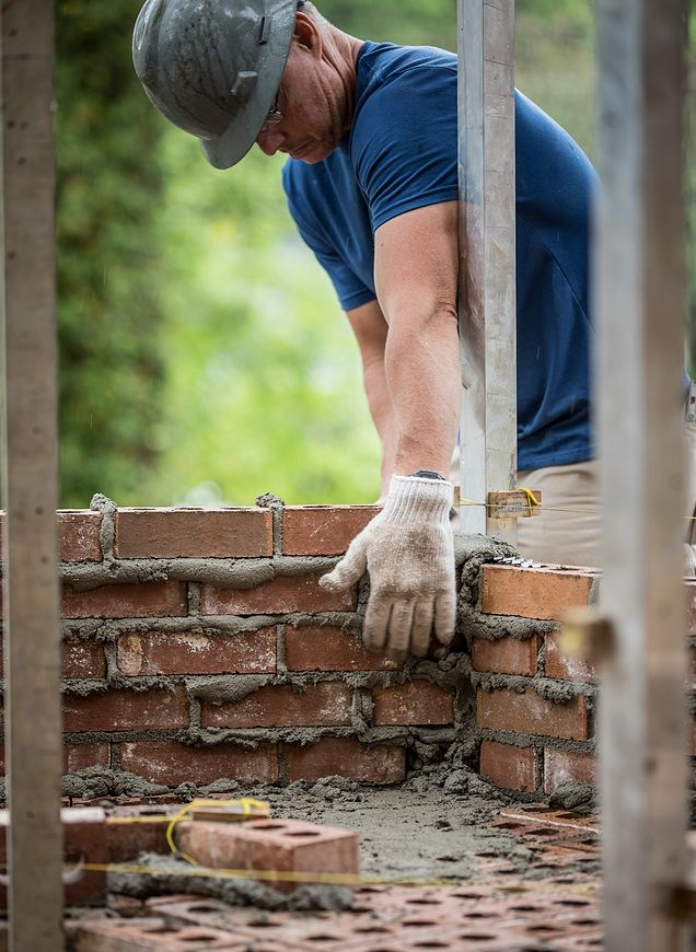 CRH mason laying structural bricks to build a foundation