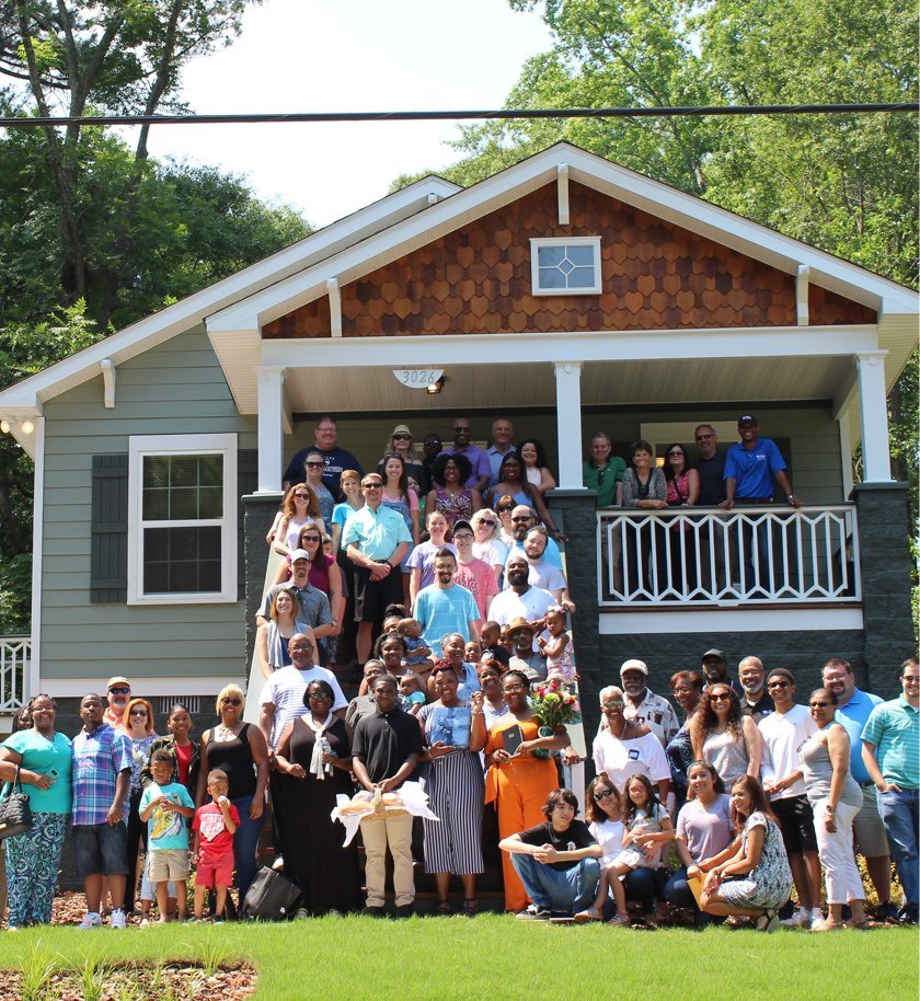 CRH employees support community events, posing with community members in front of a house