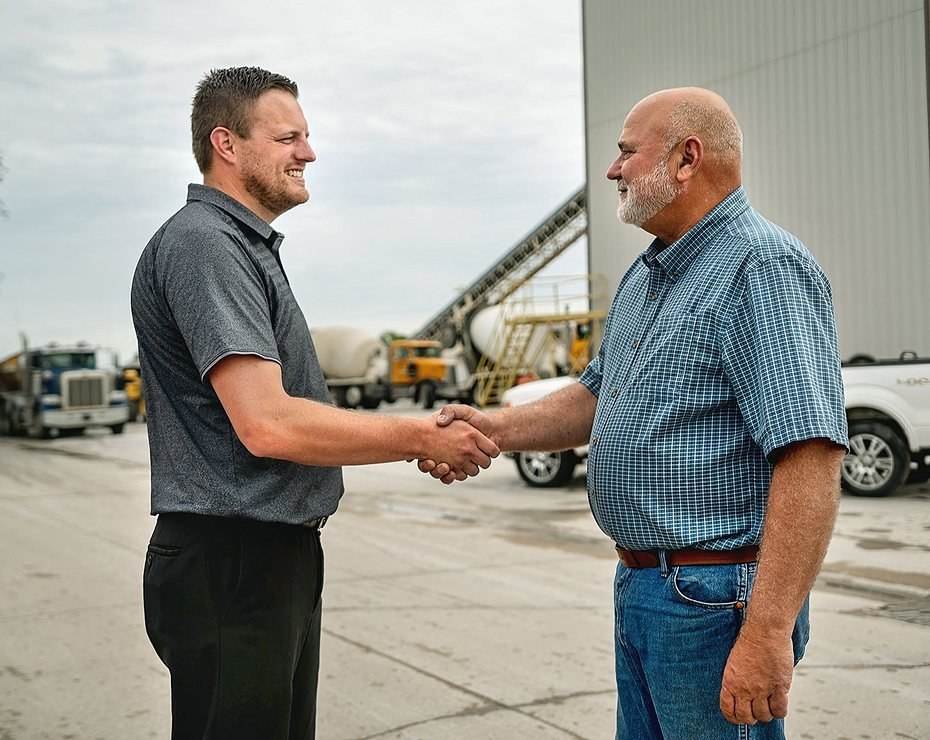 two men shaking hands on work site