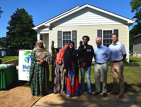 CRH employees posing with community members at a Habitat for Humanity project
