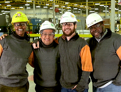 Group of diverse CRH employees posing in a production facility