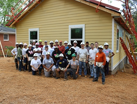 Group of CRH employees posing in front of a house at a job site