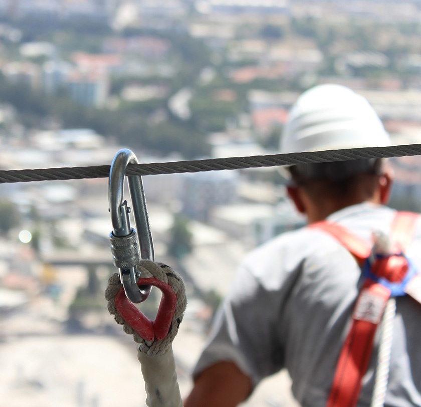 Construction worker clipped in to a harness for safety.