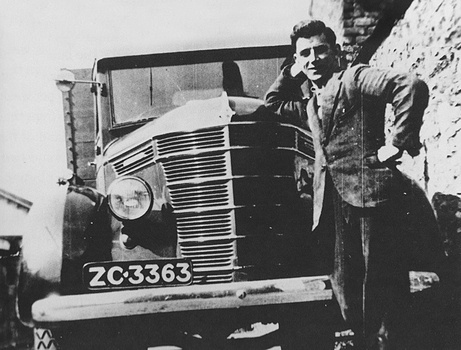 CRH founder Tom Roche leaning against a truck in 1930s Ireland