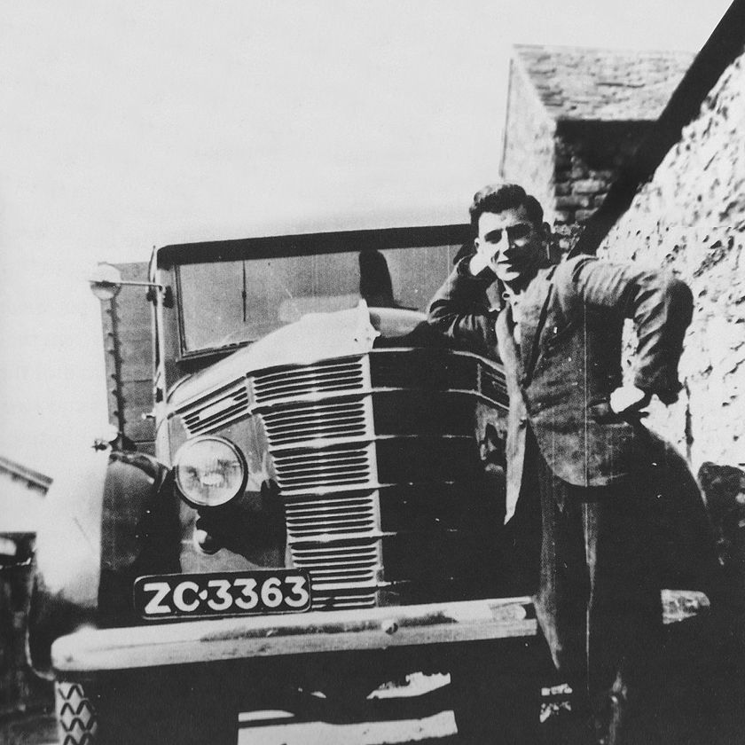 CRH co-founder Tom Roche leaning against a truck in 1930s Ireland