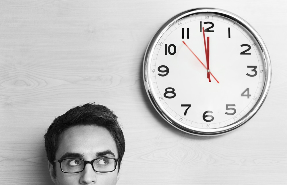 Headshot young businessman wearing spectacles looking at clock on wall in office