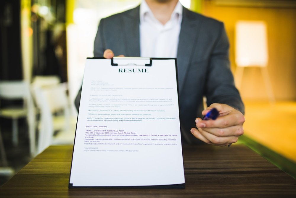 Young businessman submitting resume to employer to review