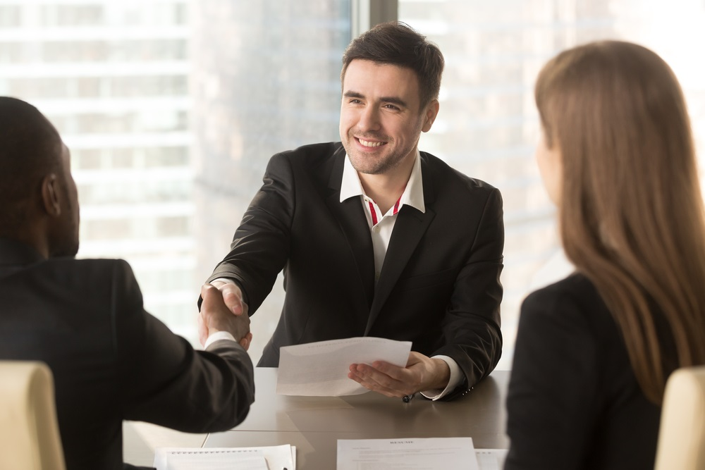 Happy applicant greeting employers at job interview